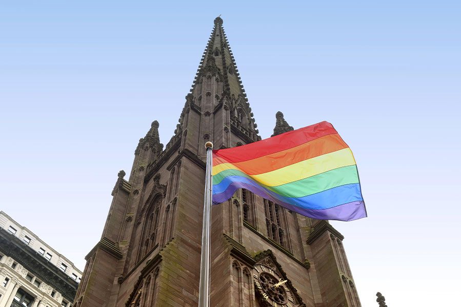 An lgbt pride flag flying in front of a church