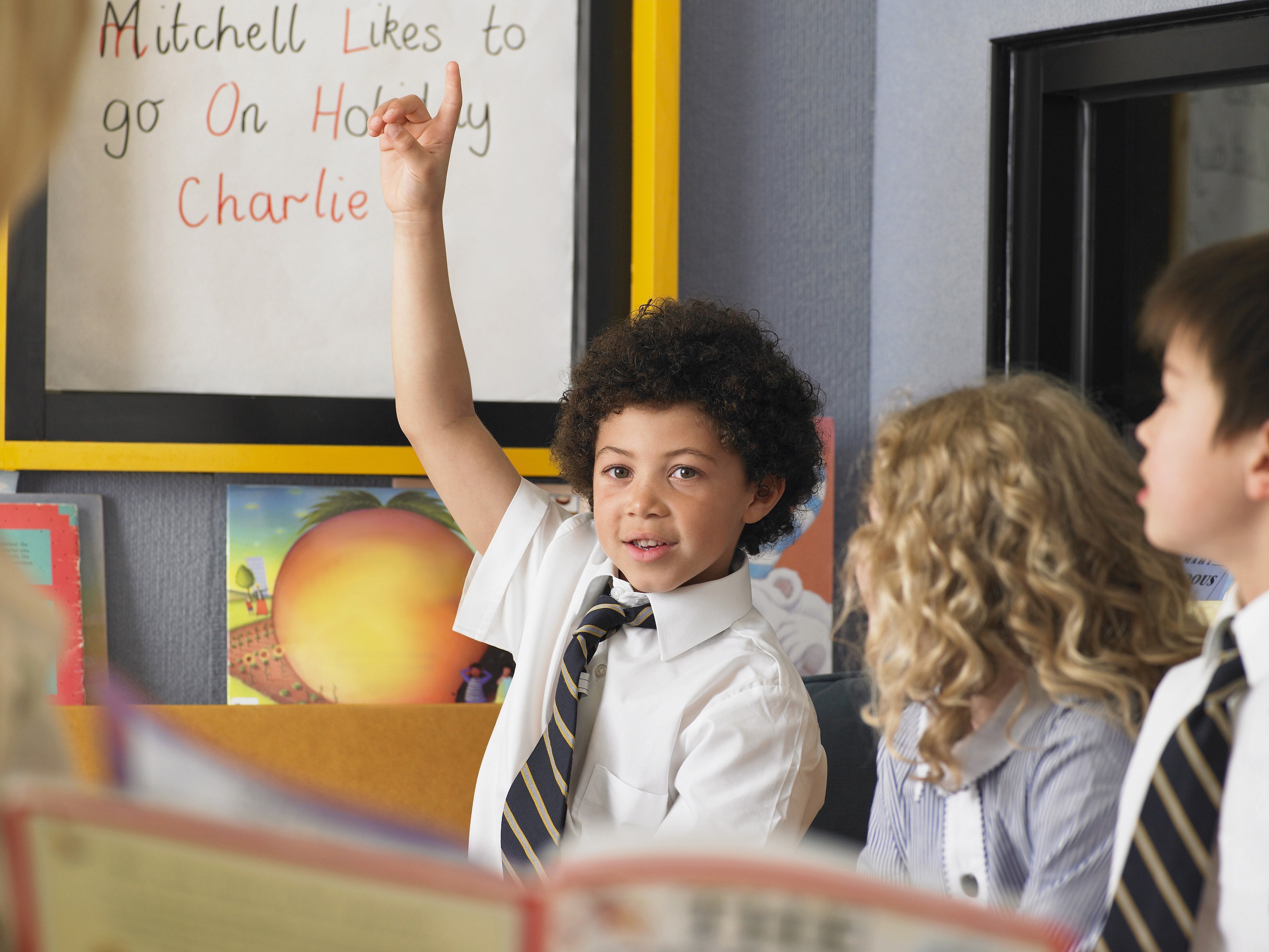 A child at a private religious school raising his hand in class.