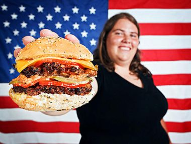 An overweight American holding a cheeseburger