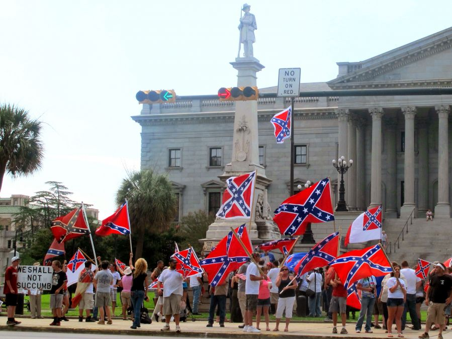 People waving Confederate flags in front of a statue