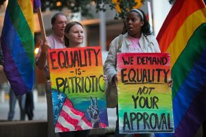 Two women hold signs protesting for LGBT equality