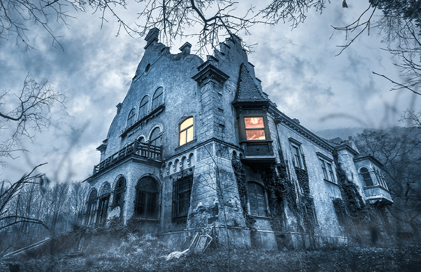 A haunted house viewed through the trees.
