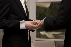 A man putting a ring on another man's finger