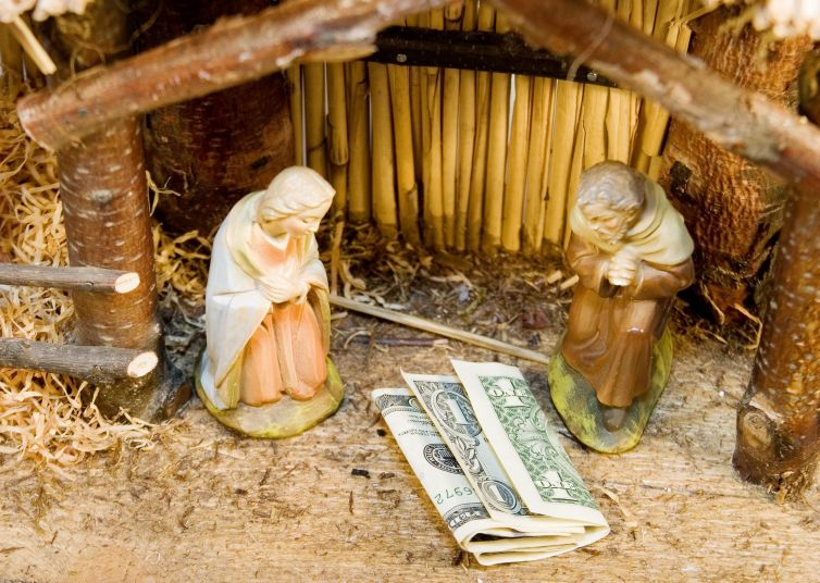 Money in a manger in place of Jesus Christ
