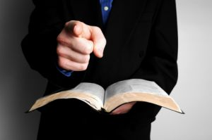 man pointing at camera with Bible in hand