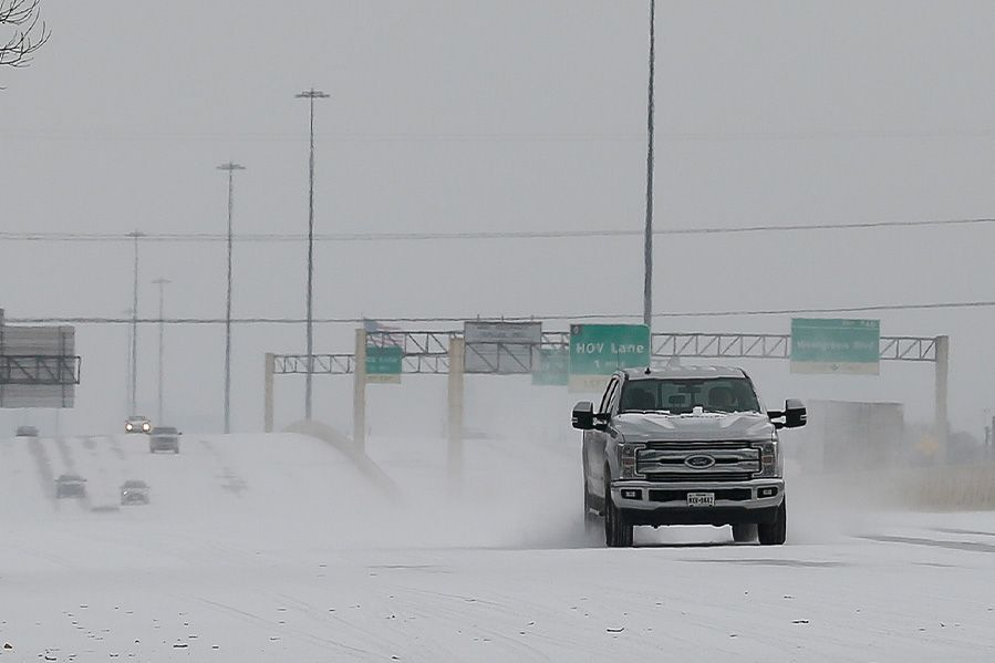 pickup truck driving in Texas snowstorm