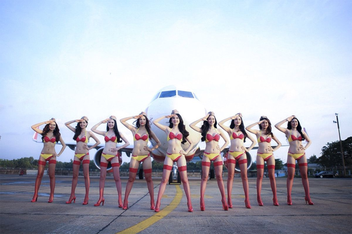 Bikini models pose in front of an airplaine