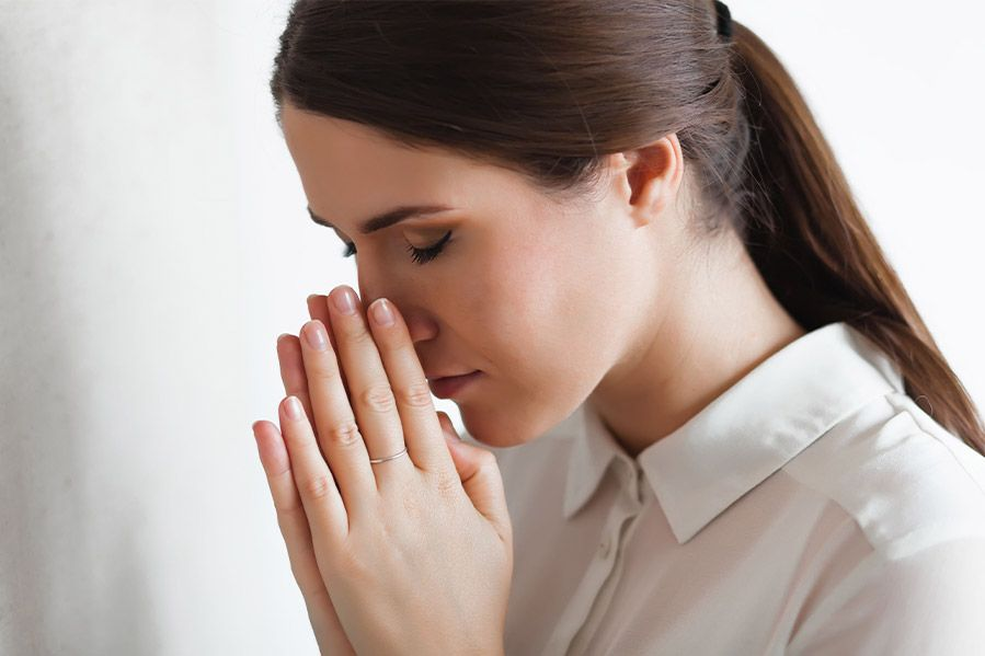 Woman's head bowed in prayer