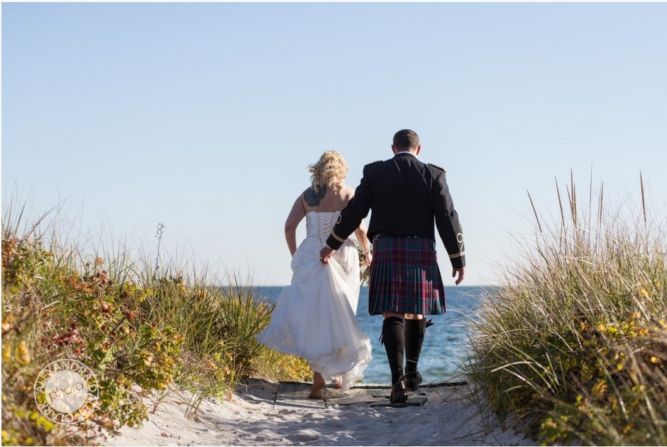 Bride and Groom walking down to the sandy beach after saying their wedding vows.