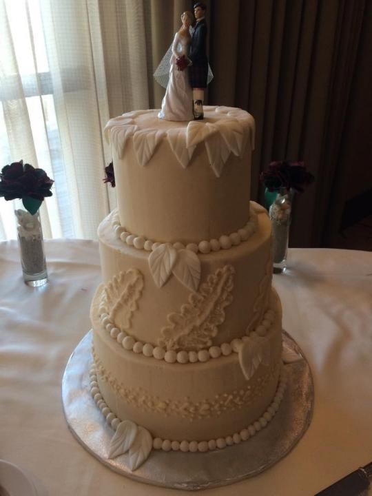 A traditional three layer wedding cake with the bride and groom on top.