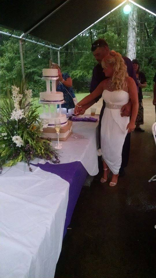 Cutting the wedding cake in unison as Husband and Wife.