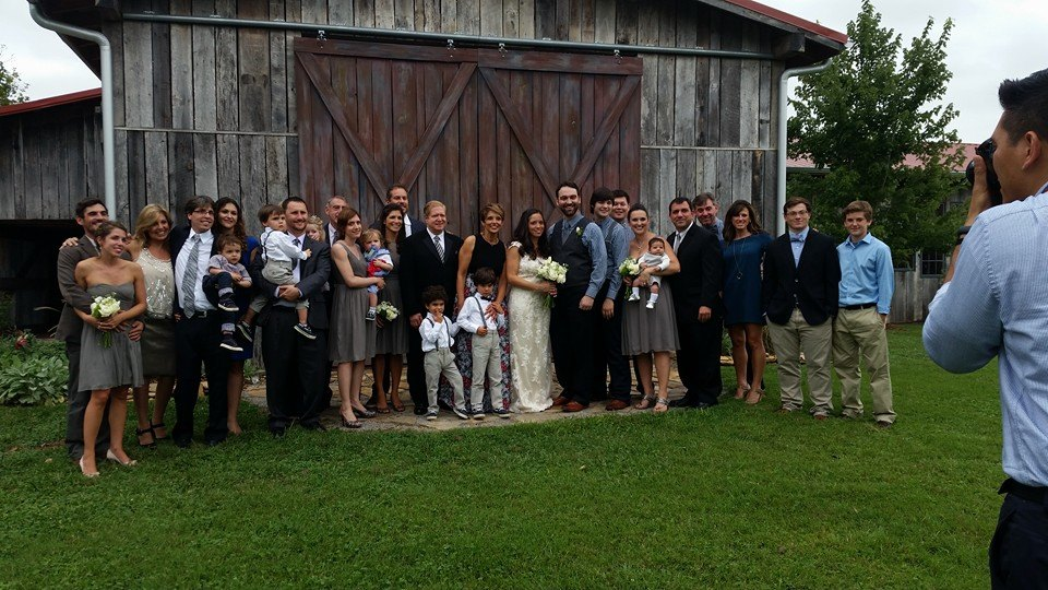 The wedding party and the whole family come together for this wedding reception photo.